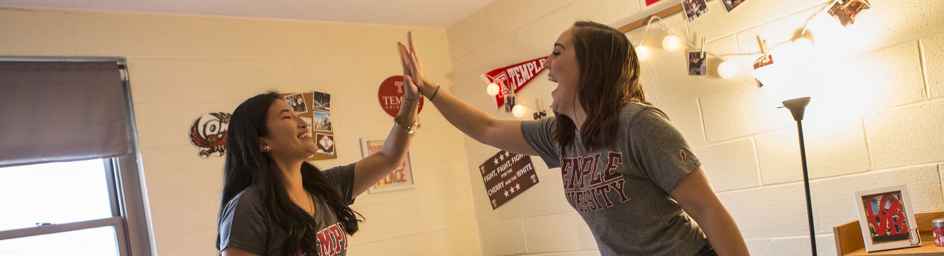 Two female students high-fiving in their on-campus residence hall
