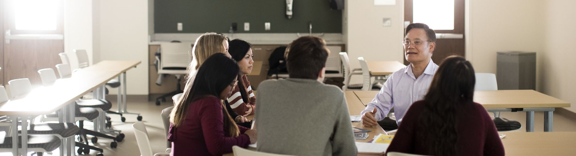 A group of students talking to a professor at a table in a classroom
