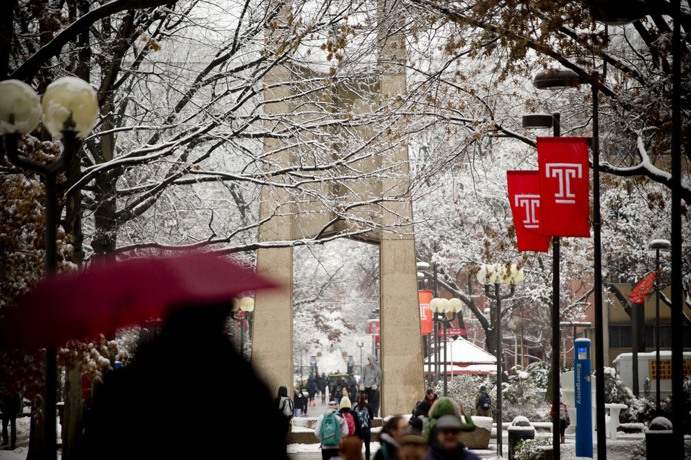 Person with umbrella walking toward the Bell Tower in the snow