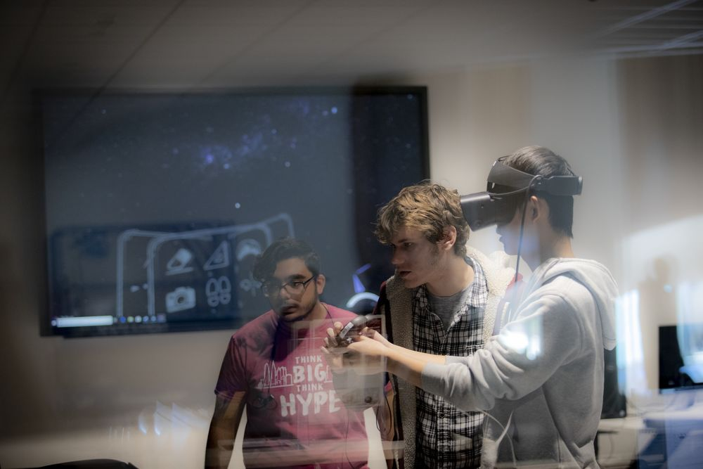 Three students using a virtual reality headset